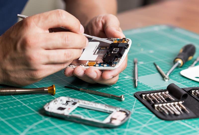 Équipez réparer le smartphone cassé, fermez-vous vers le haut de la photo image libre de droits