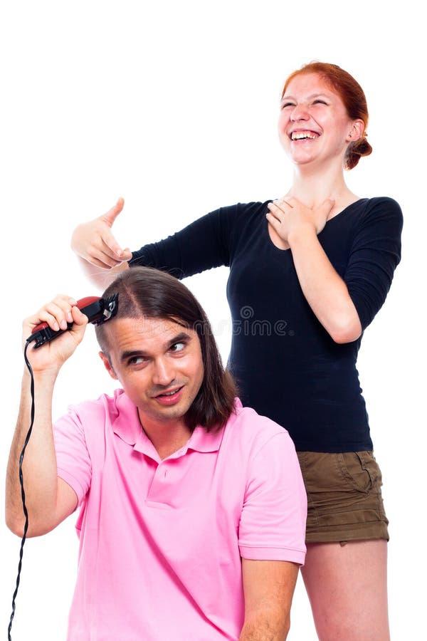 Équipez raser son cheveu et femme riant de lui image libre de droits