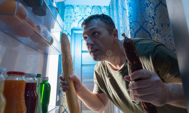 Équipez rechercher un casse-croûte dans son réfrigérateur photos libres de droits