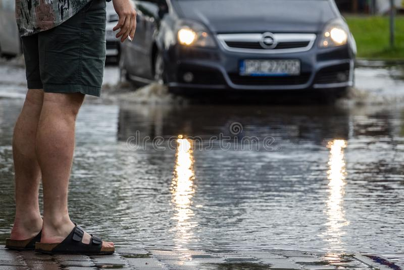 Équipez regarder la voiture sur une rue inondée images stock