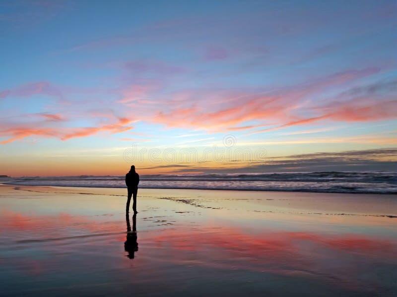 Équipez regarder le beau coucher du soleil à la plage photographie stock libre de droits