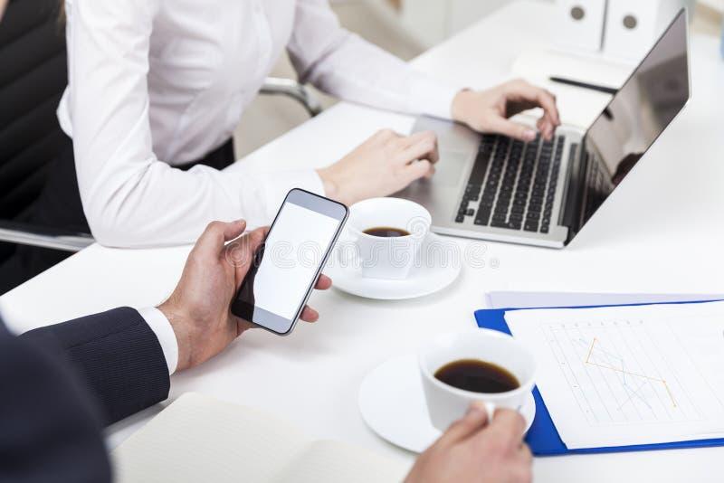 Équipez regarder son téléphone, femme introduisant au clavier le bureau image stock