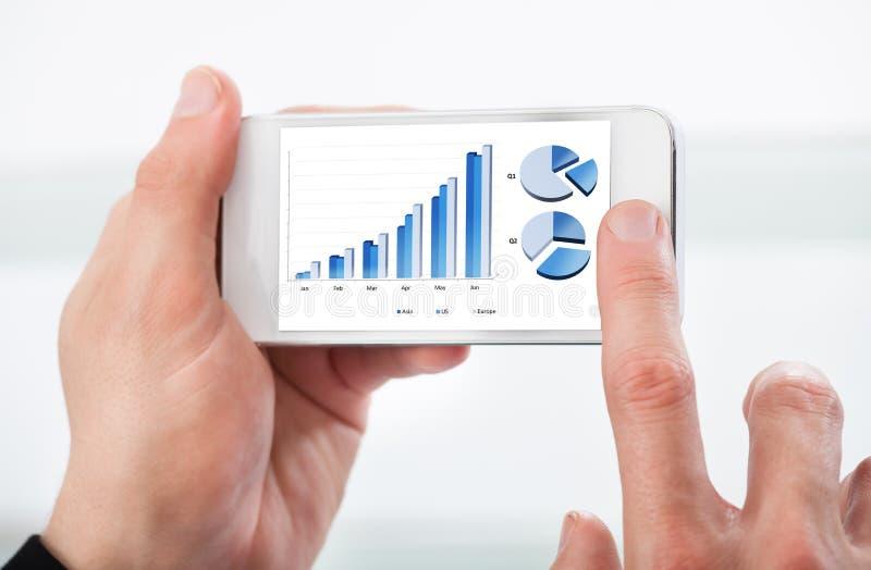 Équipez regarder un graphique à son téléphone portable image stock