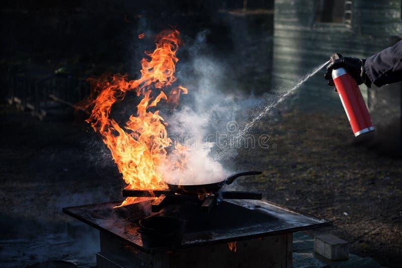 Équipez s'éteindre le feu sur une casserole de fer avec la mousse d'un pulvérisateur images libres de droits