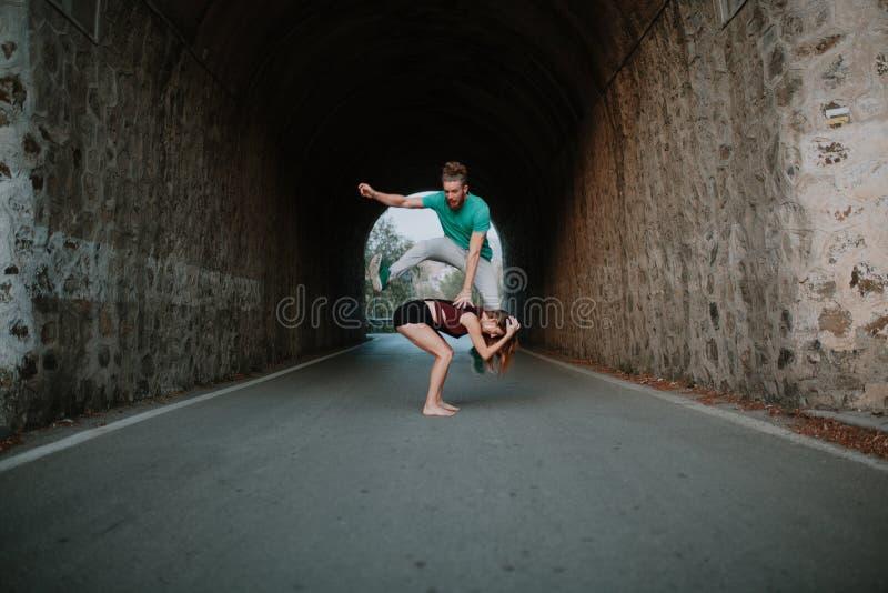 Équipez saute-mouton sautant par-dessus la femme sur une route images libres de droits