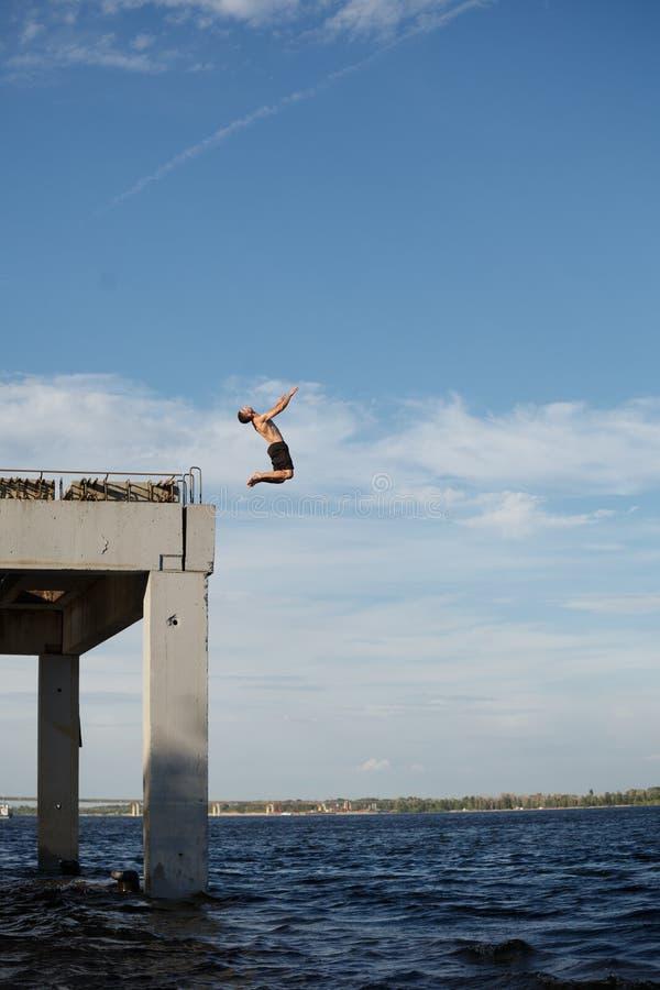 Équipez sauter dans la mer de la jetée photographie stock libre de droits