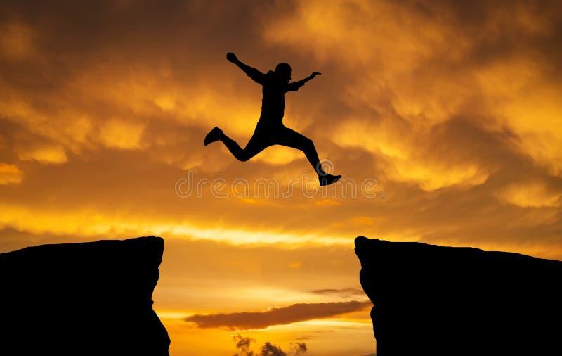 Équipez sauter par-dessus des roches avec l'espace sur le fond ardent de coucher du soleil image stock