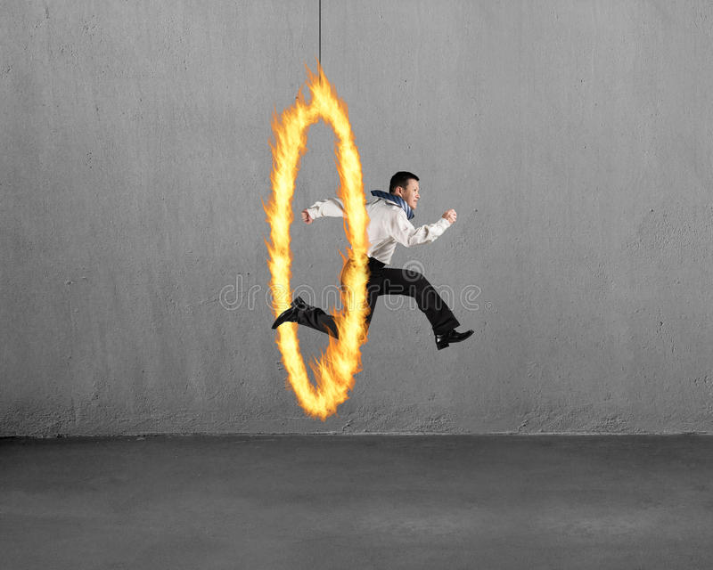 Équipez sauter par le cercle du feu avec le mur en béton image libre de droits