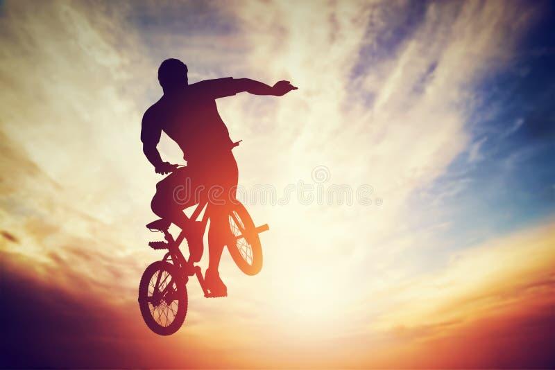 Équipez sauter sur le vélo de bmx exécutant un tour contre le ciel de coucher du soleil illustration libre de droits