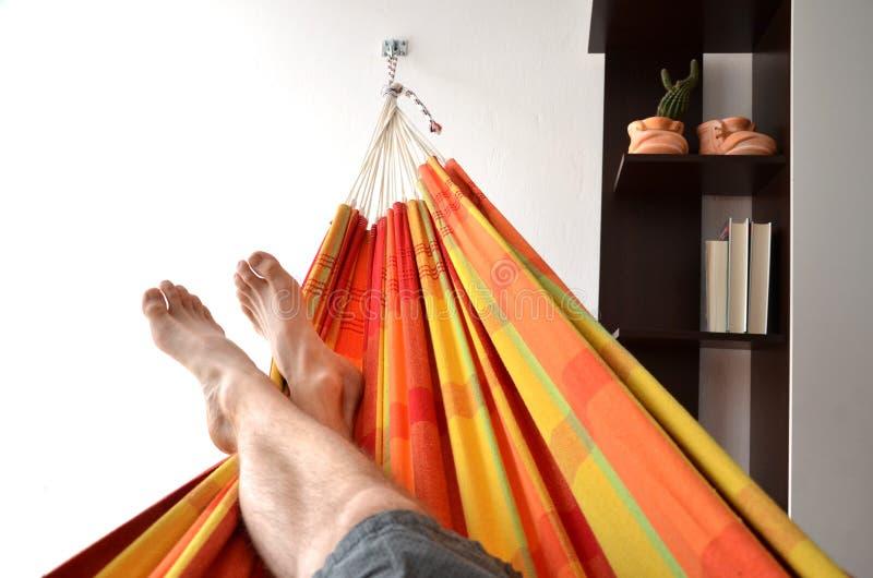 Équipez se coucher dans l'hamac lumineux fixé au mur d'intérieur dans la maison photo stock