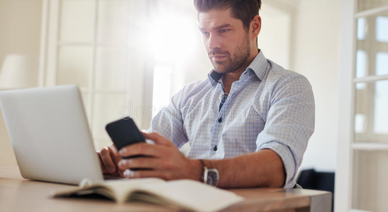 Équipez se reposer au bureau avec l'ordinateur portable et le téléphone portable à la maison photo libre de droits