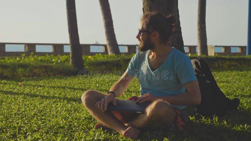 Équipez se reposer avec l'ordinateur portable en parc naturel sous un palmier photo libre de droits