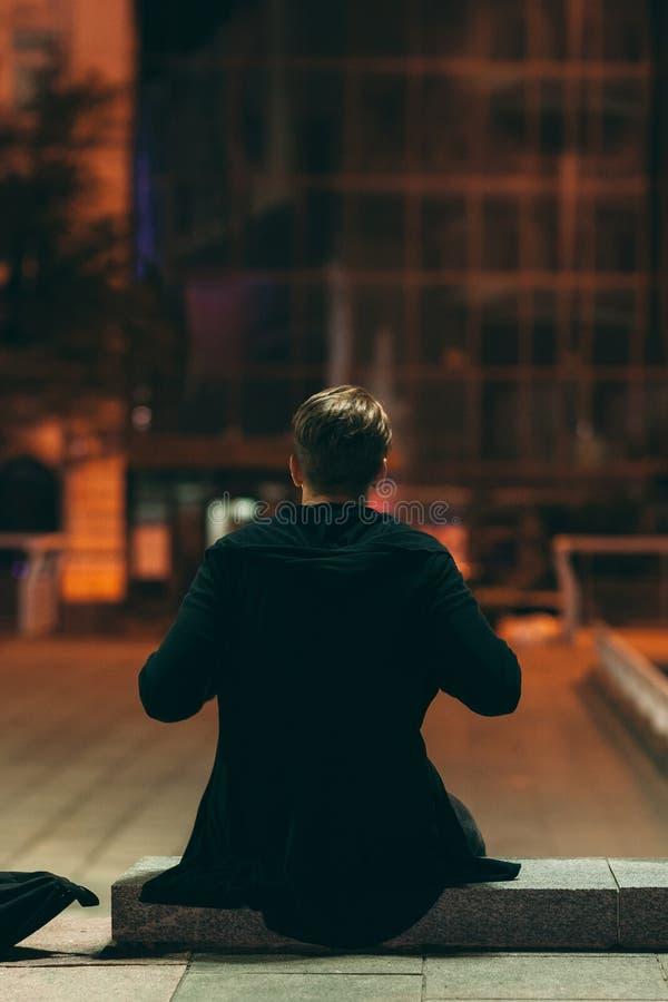 Équipez se reposer dans la rue de nuit, vue arrière images stock