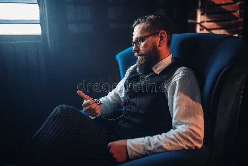 Équipez se reposer dans le fauteuil, regardant la montre de poche photographie stock libre de droits