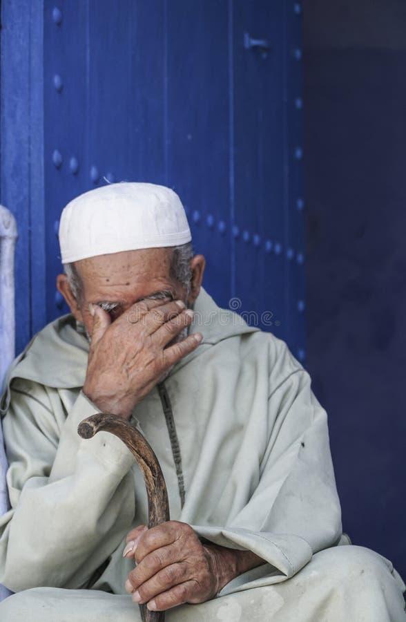 Équipez se reposer devant une porte bleue dans Chefchaouen, Maroc photographie stock libre de droits