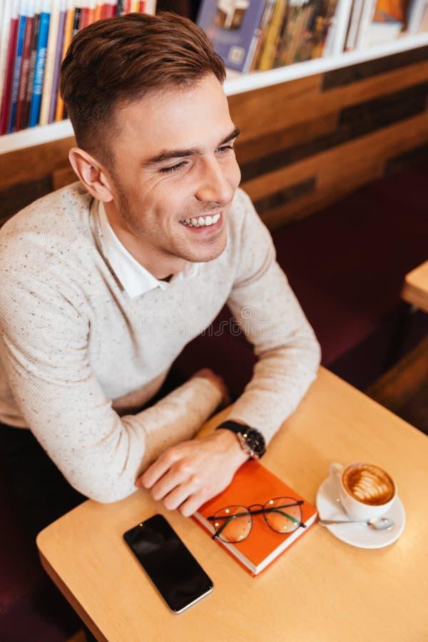 Équipez se reposer en café avec la tasse du café et du livre photos libres de droits