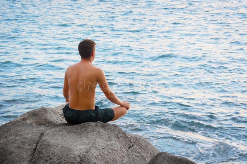Équipez se reposer en position de lotus et regarder la mer photos stock
