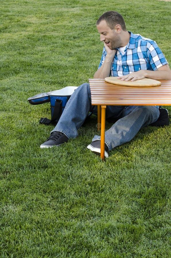 Équipez se reposer sur l'herbe dehors devant une table avec un refroidisseur photographie stock libre de droits