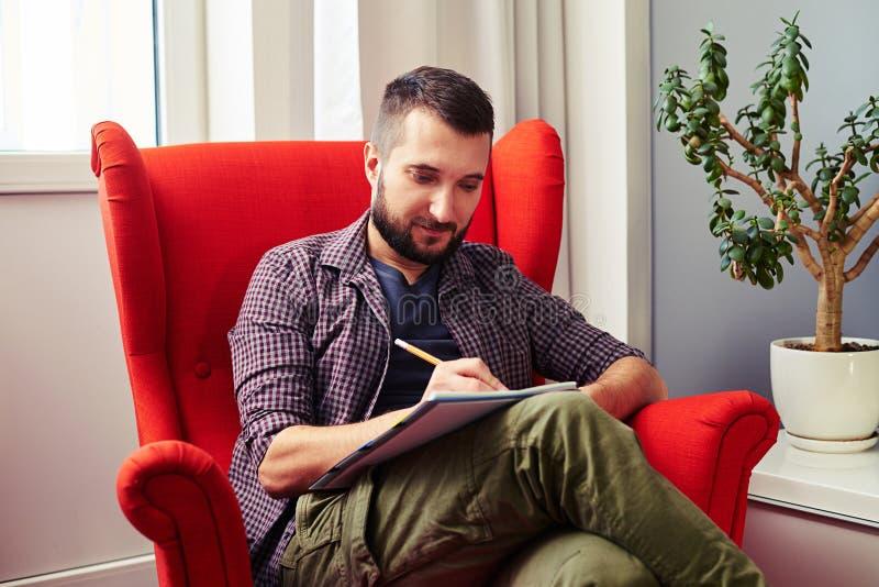 Équipez se reposer sur la chaise rouge et écrire quelque chose photos stock