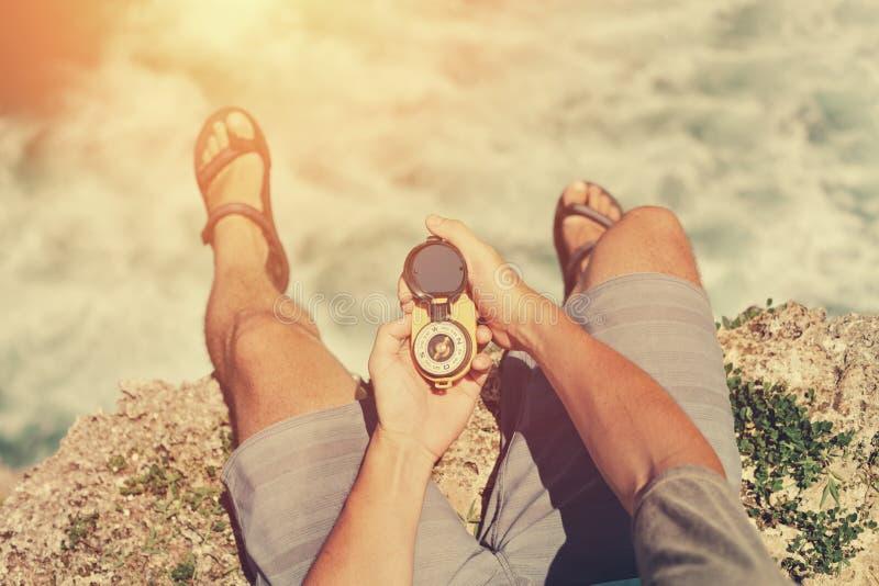 Équipez se reposer sur la falaise avec la boussole au-dessus de l'océan photographie stock