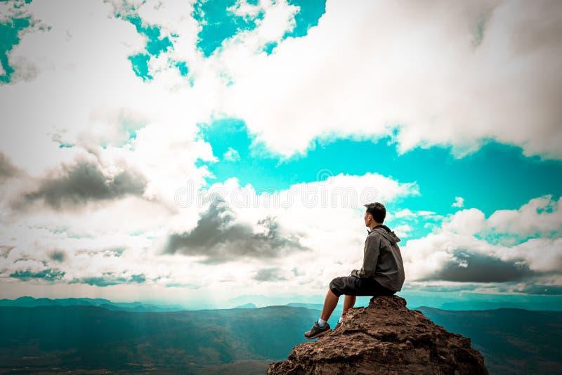 Équipez se reposer sur la roche au sommet de la montagne regardant au ciel image libre de droits