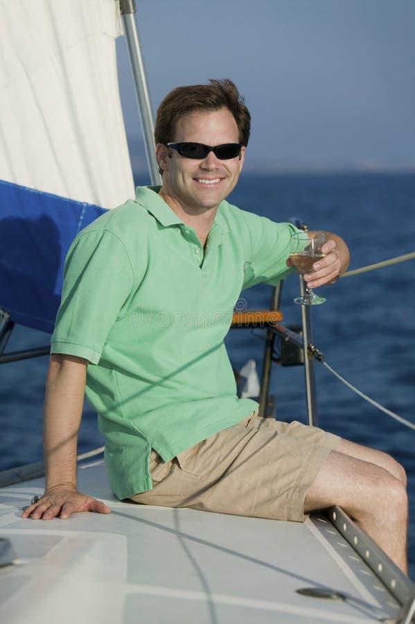 Équipez se reposer sur le bateau à voiles, buvant du vin blanc images stock