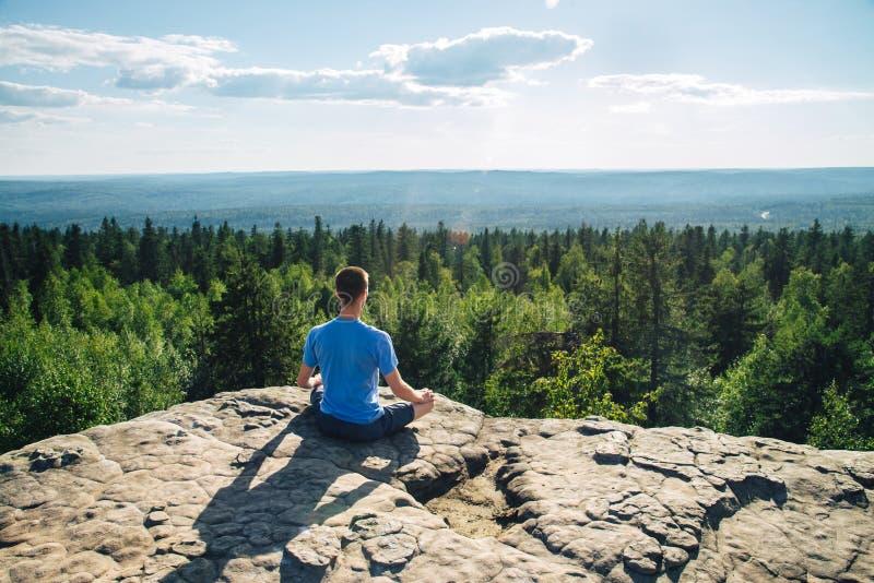 Équipez se reposer sur le dessus de la montagne en session de méditation en Lotus Posture, padmasana, pratiquant le pranayama photos stock
