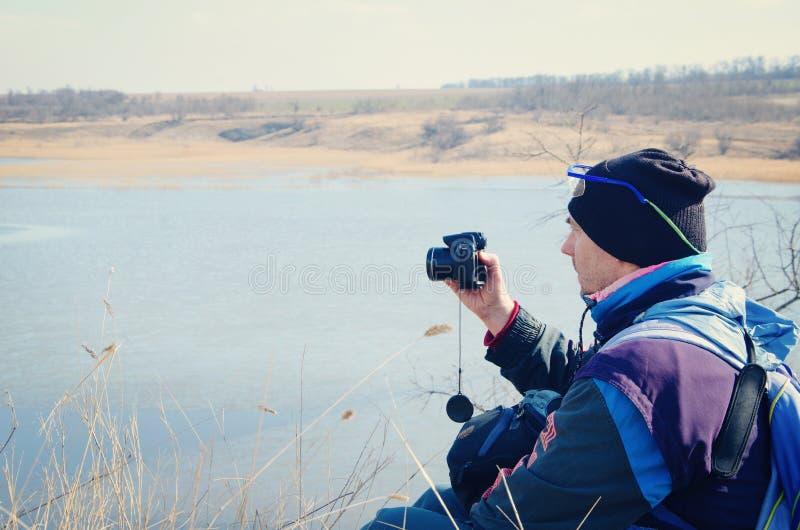 Équipez se reposer sur le lac avec un appareil-photo dans des ses mains photo libre de droits