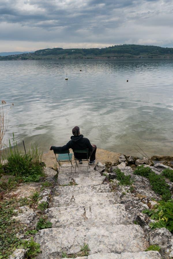 Équipez se reposer sur une chaise aux rivages d'un beau lac une soirée calme de ressort avec des escaliers de roche menant vers l photographie stock libre de droits