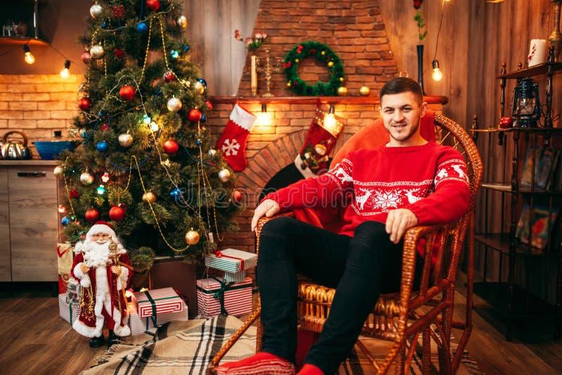 Équipez se reposer sur une chaise près de la cheminée, Noël photographie stock libre de droits