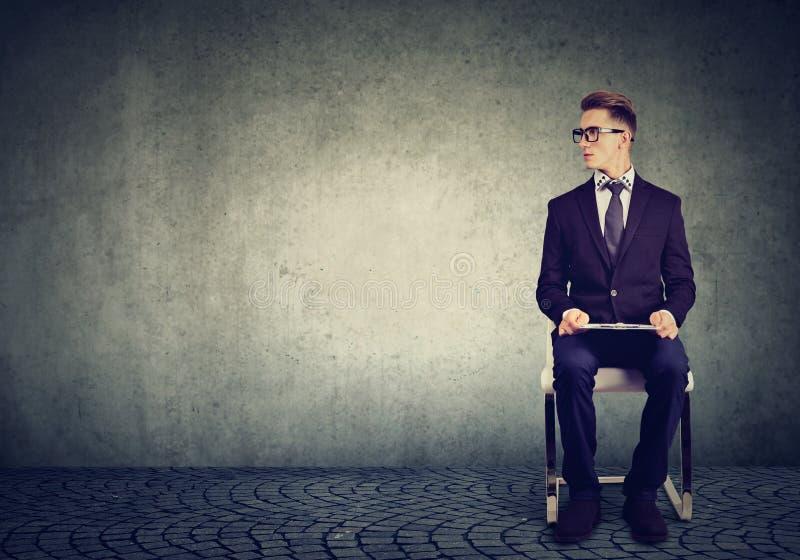 Équipez se reposer sur une entrevue d'emploi de attente de chaise image stock