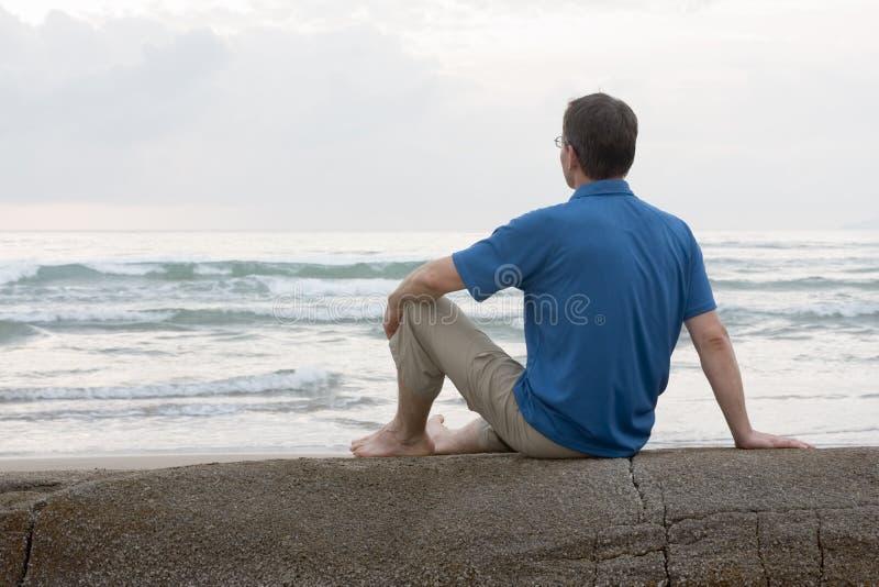 Équipez se reposer sur une roche à la mer photographie stock