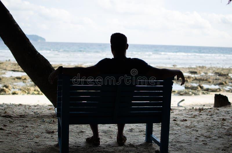 Équipez seul se reposer sur un banc près du bord de la mer image stock