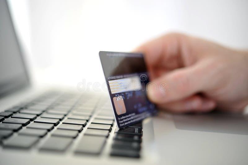 Équipez tenir des achats et des opérations bancaires en ligne disponibles de carte de crédit photographie stock
