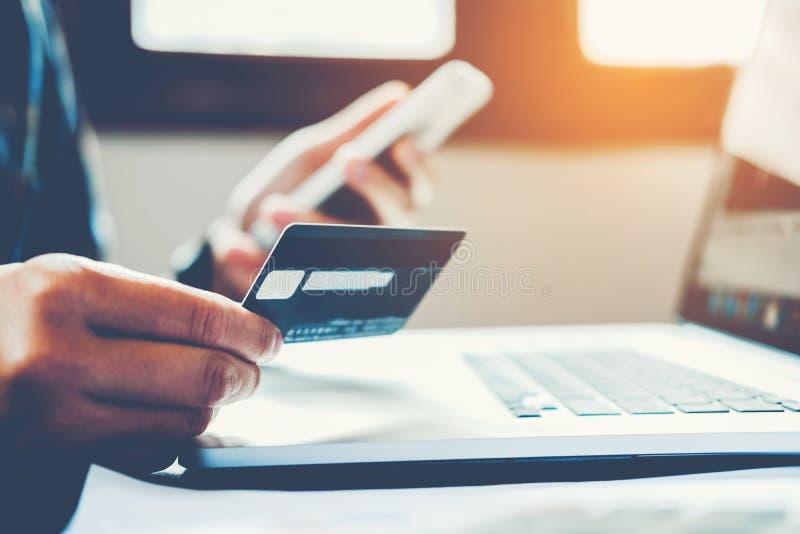 Équipez tenir la carte de crédit et à l'aide du téléphone portable tenant la carte de crédit photos stock