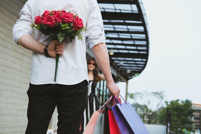 Équipez tenir le panier et le bouquet des roses rouges derrière le sien de retour image libre de droits