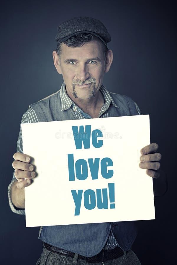 Équipez tenir le signe avec les mots que nous vous aimons photos libres de droits