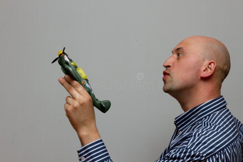Équipez tenir un avion vert et rêver le vol d'aboyt image stock
