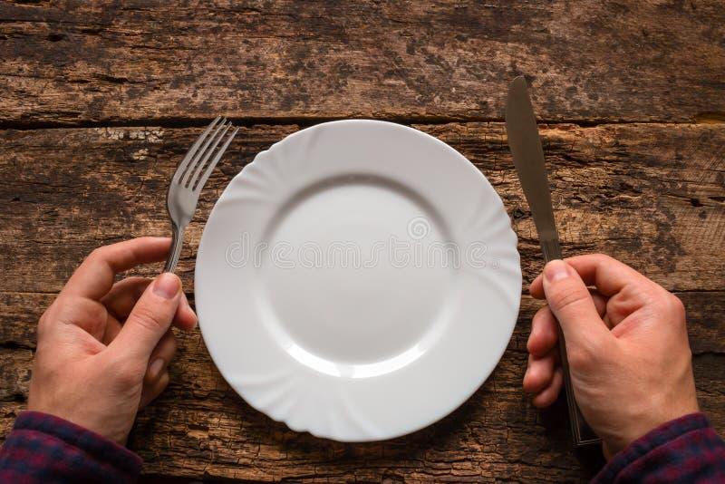 Équipez tenir un couteau et une fourchette à côté du plat sur un en bois photo libre de droits