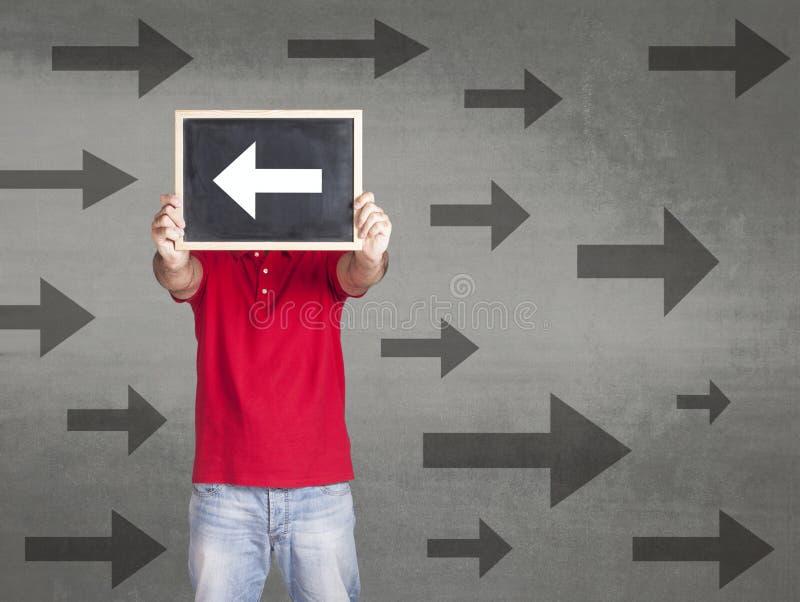 Équipez tenir un signe de flèche se dirigeant dans la direction opposée photo libre de droits