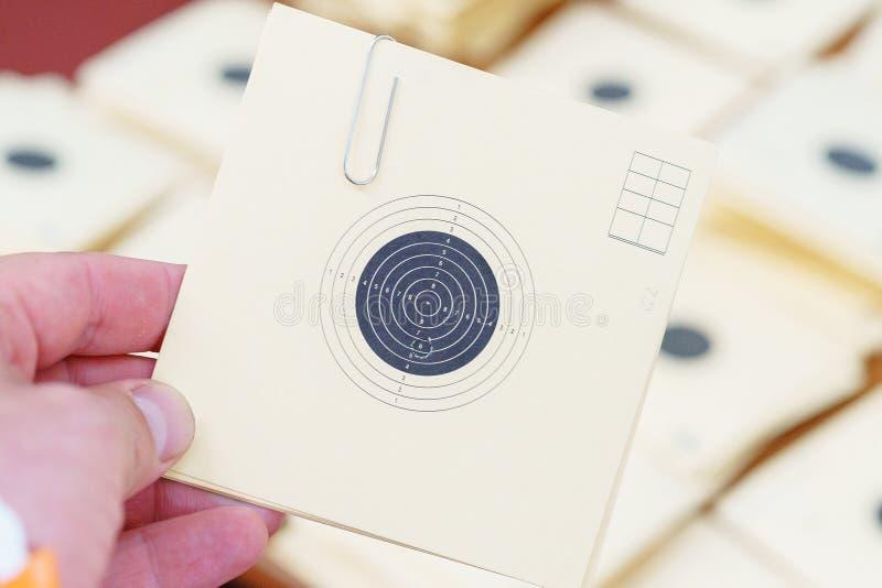 Équipez tenir une cible de papier à un champ de tir avec un trou photos stock