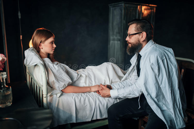 Équipez tenir une main de femme aimée par malade dans le lit photographie stock libre de droits