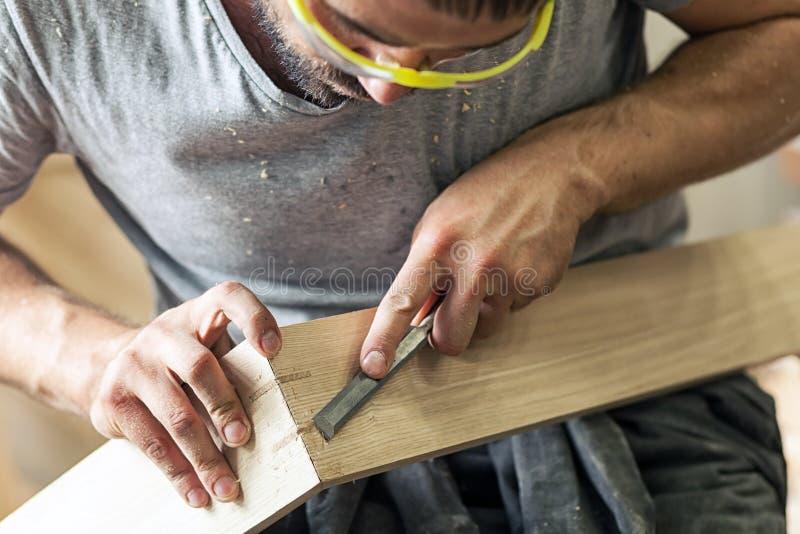 Équipez traiter un produit en bois avec un burin images libres de droits
