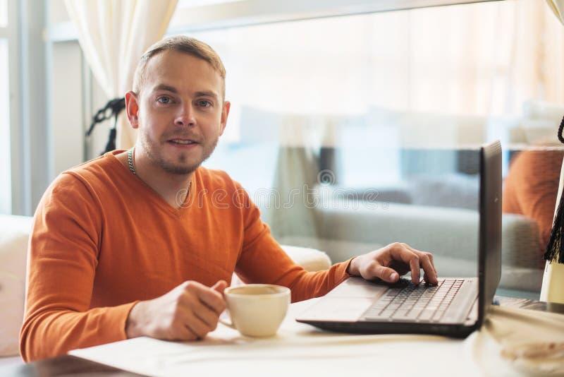 Équipez travailler au carnet, regard à l'appareil-photo, en café image stock