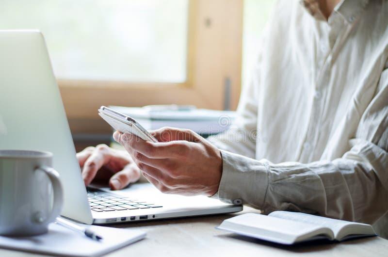 Équipez travailler sur l'ordinateur portable, avec la tasse du café et du téléphone image libre de droits