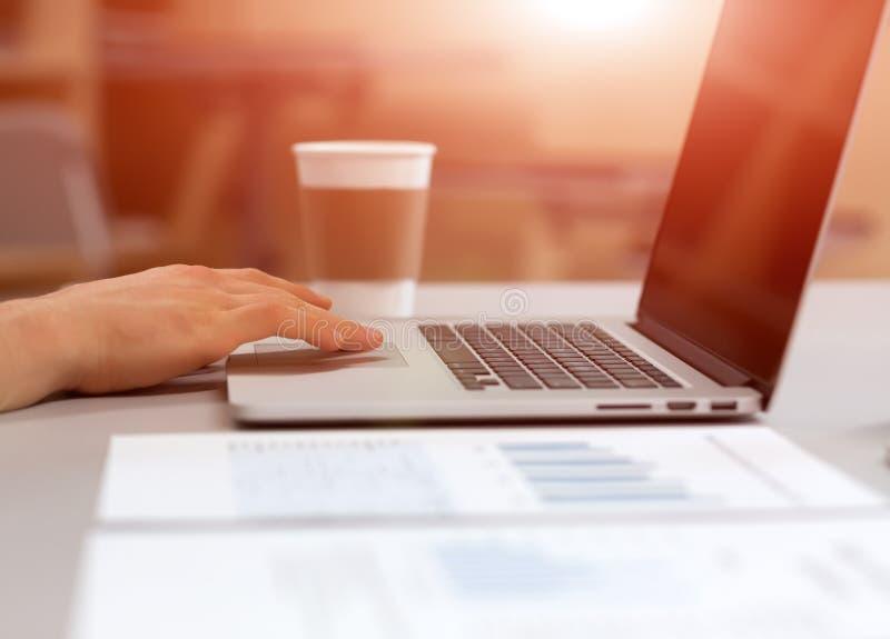 Équipez travailler sur l'ordinateur portable dans l'environnement confortable avec du café photographie stock libre de droits