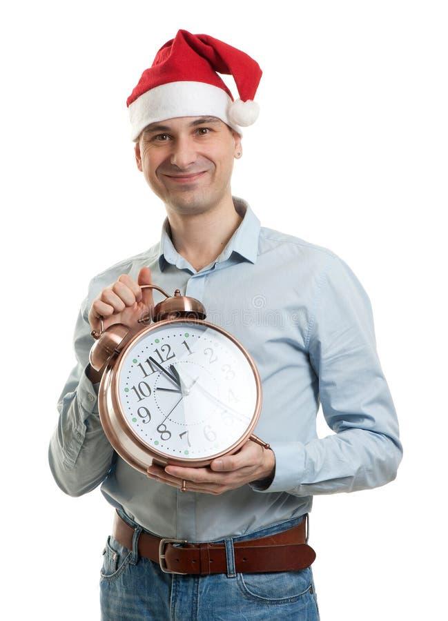 Équipez utiliser un chapeau de Santa avec la grande horloge images stock