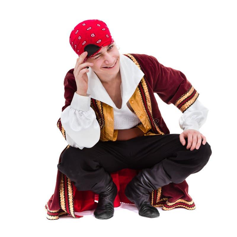 Équipez utiliser un costume de pirate posant, sur le blanc photographie stock