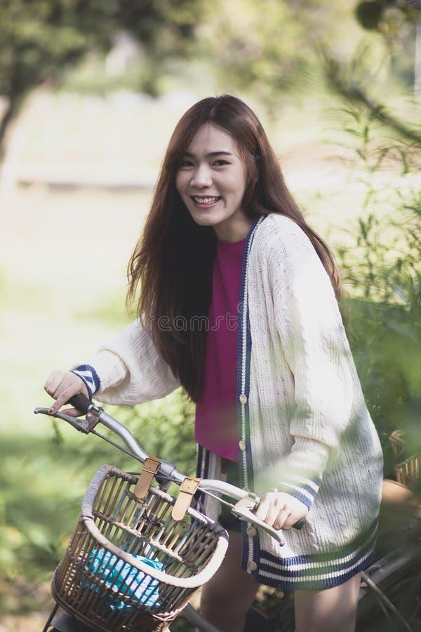Équitation asiatique gaie de plus jeune femme sur la rétro bicyclette en parc vert image libre de droits