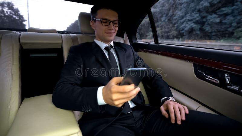 Équitation avec plaisir d'homme d'affaires sur la banquette arrière de la voiture chère, utilisant l'appli de téléphone photo stock